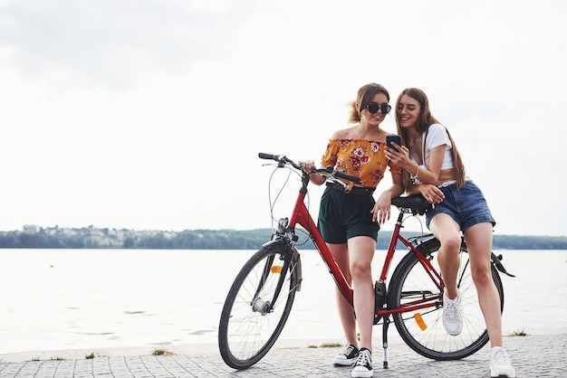 Two female friends on the bike have fun at beach near the lake.