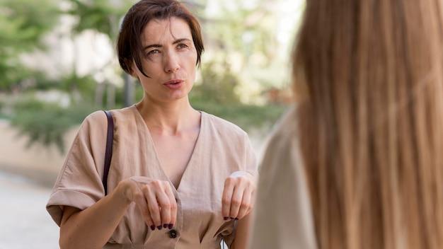 手話を使用して屋外で通信する2人の女性の友人
