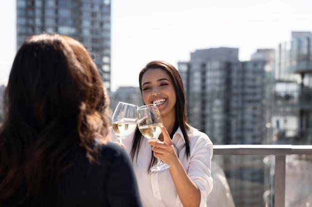 Две подруги разговаривают и наслаждаются вином на террасе на крыше