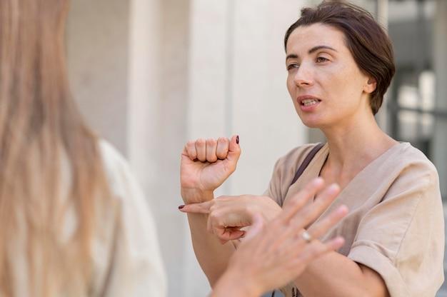Две подруги разговаривают на открытом воздухе, используя язык жестов