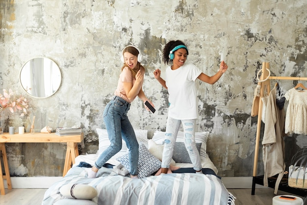 Two female friends dancing together on bed while listening to music