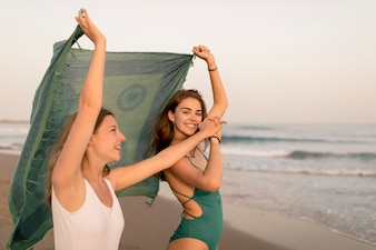 Two female friends dancing with scarf at seashore