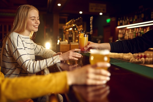 Two female friends drinks alcohol at the counter in bar. group of people relax in pub, night lifestyle, friendship, event celebration