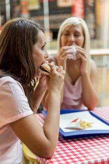 レストランでハンバーガーを一緒に食べる2人の女性の友人