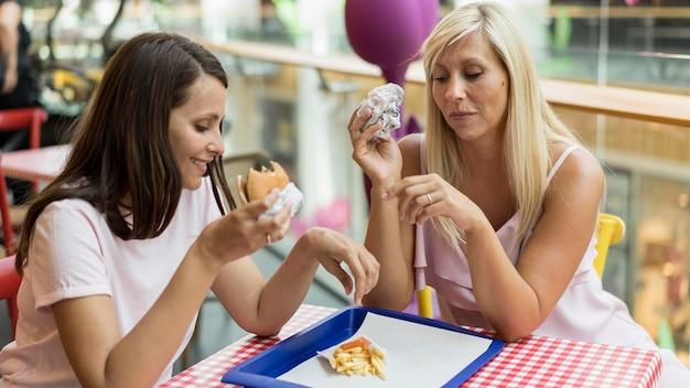Due amici femminili che mangiano hamburger con patatine fritte al ristorante