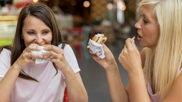 Two female friends eating burgers with fries at restaurant