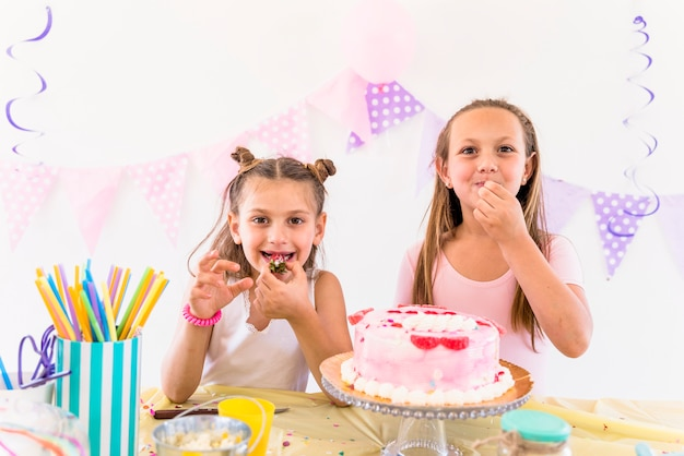 Two female friends eating cake while enjoying in birthday party