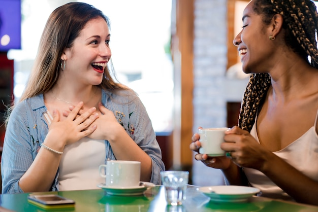 Two female friends enjoying a cup of coffee together.