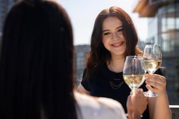 Две подруги пьют вино на террасе на крыше
