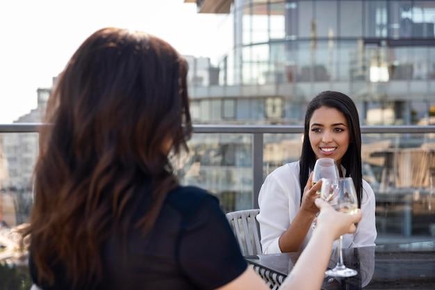옥상 테라스에서 와인을 즐기는 두 여자 친구