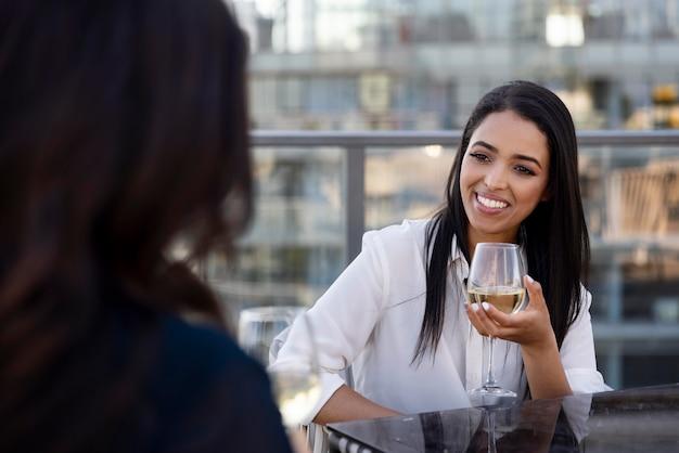 옥상 테라스에서 함께 와인을 즐기는 두 여자 친구