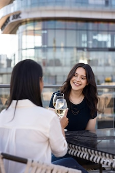 Две подруги вместе пьют вино на террасе на крыше