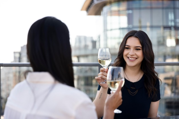 Two female friends enjoying some wine together on a rooftop terrace