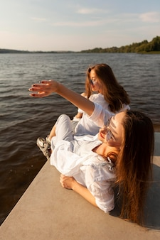 Two female friends enjoying the sun by the lake