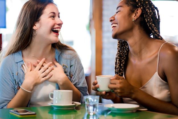 두 여자 친구가 커피숍에서 커피 한 잔을 마시며 함께 시간을 즐기고 있습니다. 친구 개념입니다.
