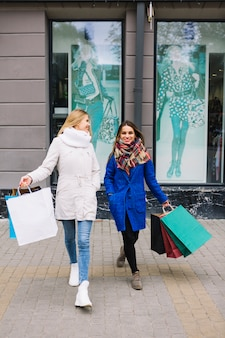 Two female friends in fashionable winter coat holding colorful shopping bags