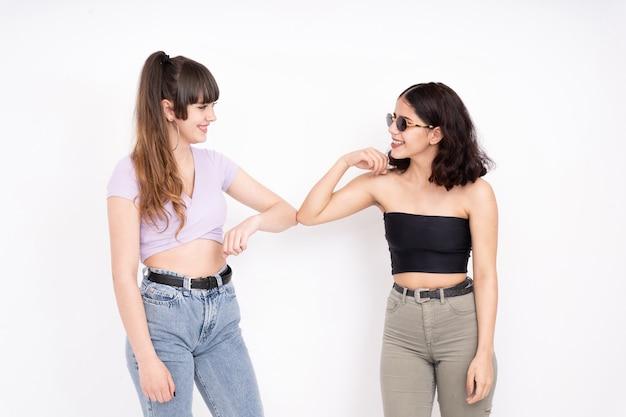 화이트에 팔꿈치와 함께 서로 인사하는 두 여자 친구
