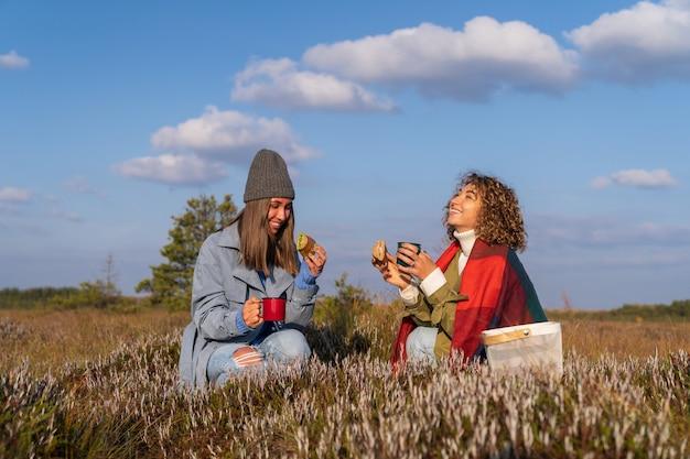자연 속에서 행복한 주말을 보내는 두 여자 친구는 가을 늪에서 크랜베리를 따며 간식을 먹습니다