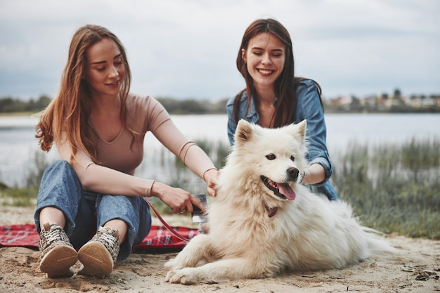Two female friends have a great time spending on a beach with cute dog.