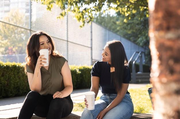 公園で一緒にコーヒーを飲んでいる2人の女性の友人
