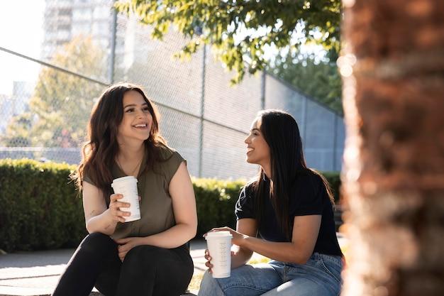 Due amiche che bevono una tazza di caffè insieme al parco