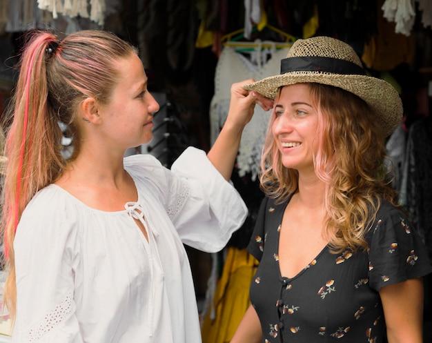 Две подруги вместе веселятся на блошином рынке