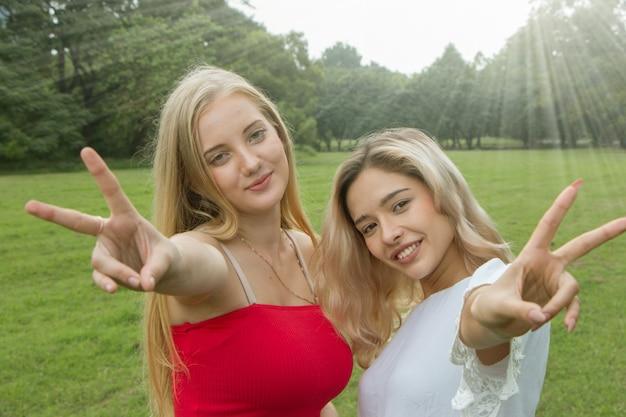 Two female friends having fun in park.