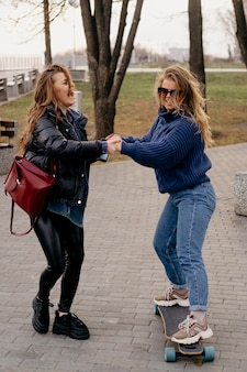 Two female friends having fun skateboarding outdoors
