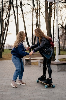 Two female friends having fun skateboarding in the park