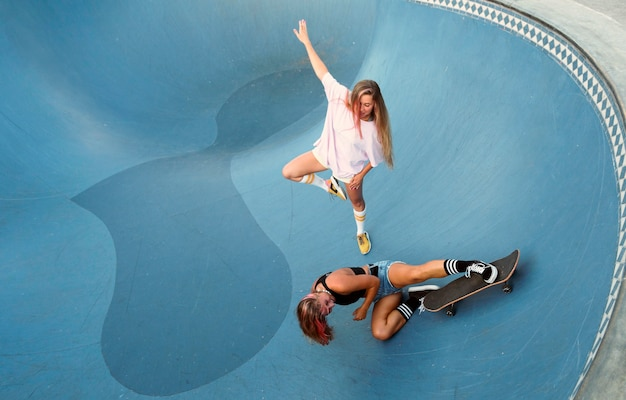 Two female friends having fun skateboarding