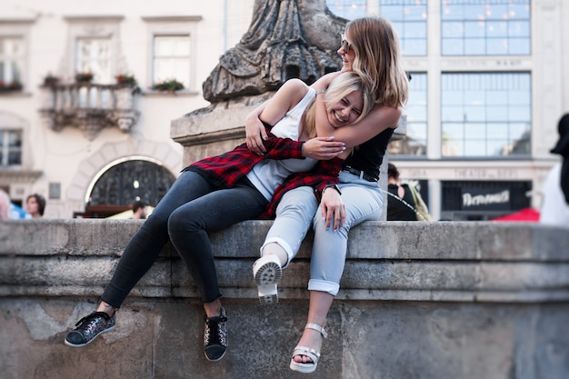 Two female friends having fun together while traveling in the city