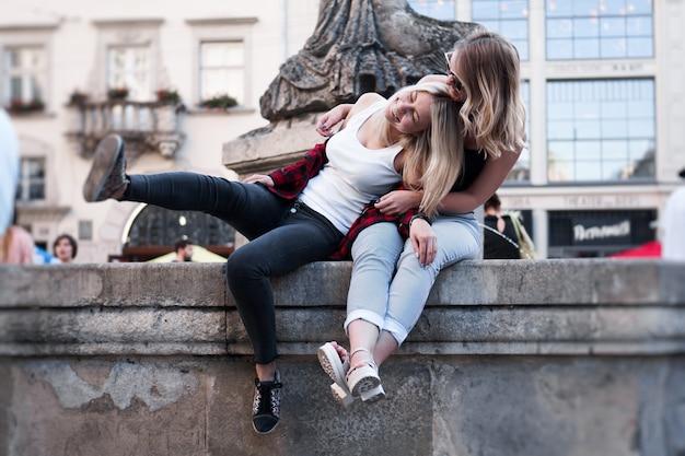 Две подруги веселятся вместе во время путешествия по старому городу