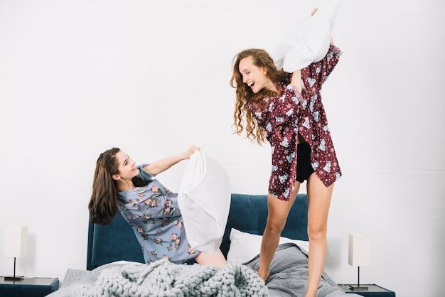 Due amici femminili divertendosi con il cuscino sul letto