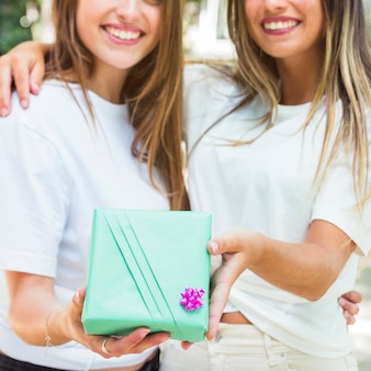 Two female friends holding green gift box
