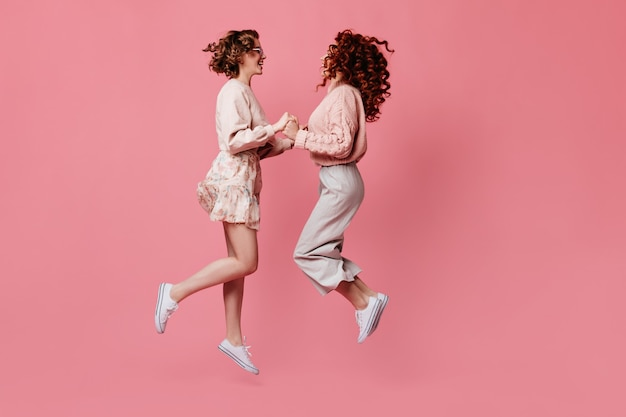 Two female friends holding hands and looking at each other. side view of amazing girls jumping on pink background.