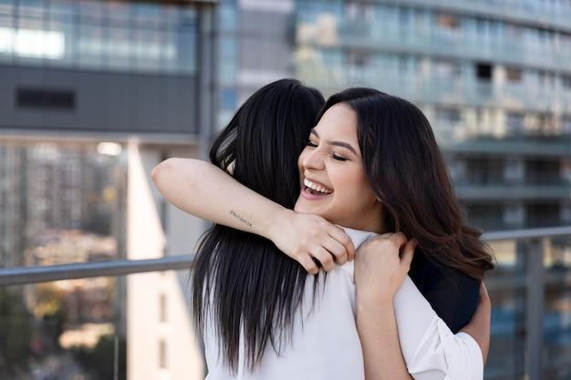 Две подруги обнимаются после встречи на террасе на крыше