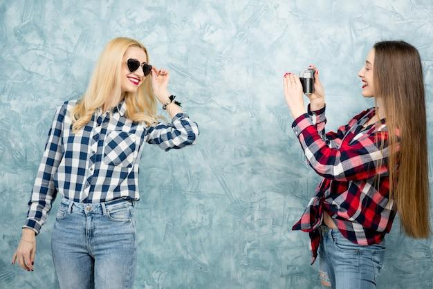 체크 무늬 셔츠와 청바지를 입은 두 명의 여자 친구가 파란색으로 칠해진 벽 배경에 복고 카메라로 사진을 찍고 있다