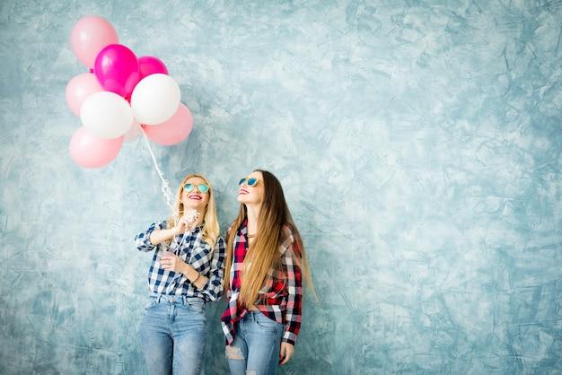 青い壁の背景に気球を楽しんでいる市松模様のシャツを着た2人の女性の友人