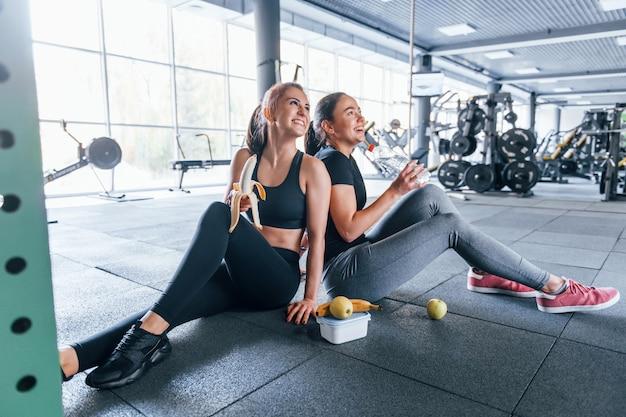 スポーツ服を着た2人の女性の友人がジムで果物を食べて休憩しています。