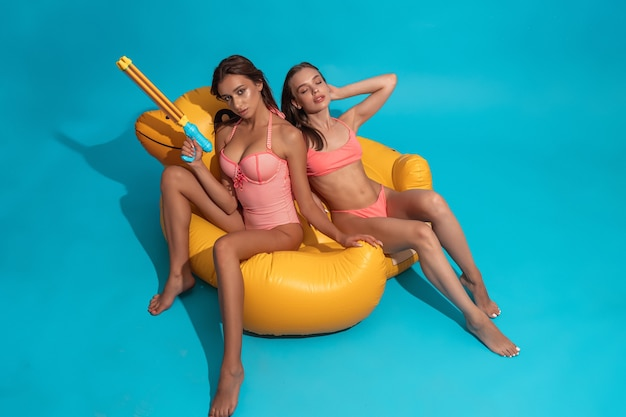 Две подруги в купальниках, сидя на надувной утке на синей стене