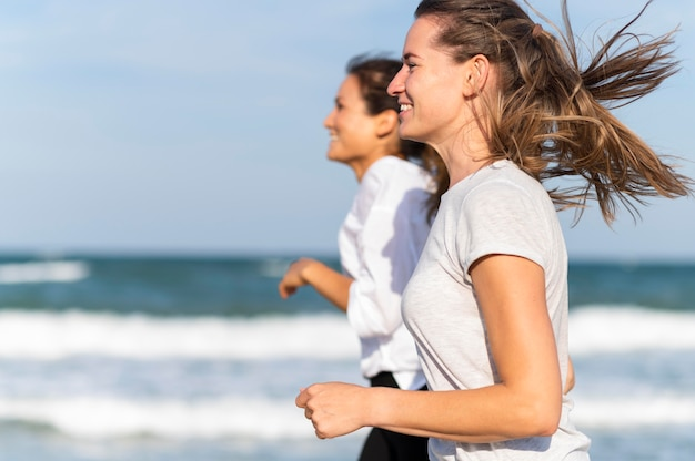 Two female friends jogging together on the beach