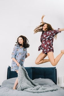Two female friends jumping on bed in bedroom