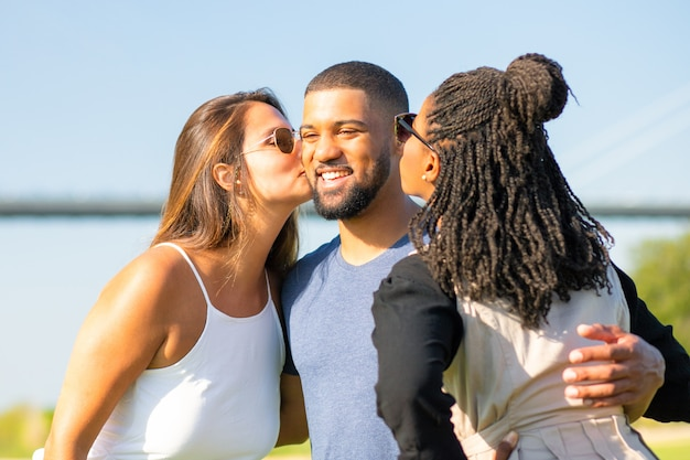 Two female friends kissing african american man on meadow. three friends spending time together in park. friendship