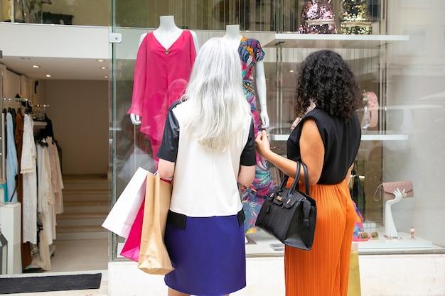 Due amiche guardando i vestiti in vetrina, tenendo i sacchetti, in piedi al negozio fuori. vista posteriore. concetto di acquisto di finestre