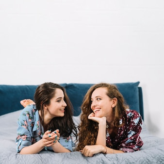 Two female friends looking at each other while lying on bed