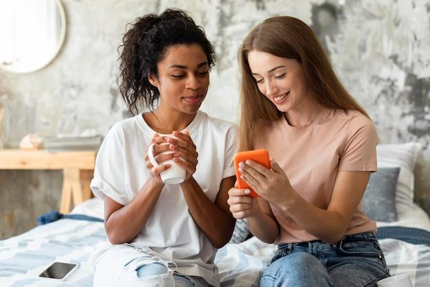 Due amiche che esaminano smartphone mentre sorseggiano un drink