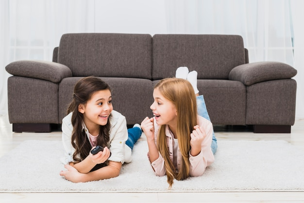 Two female friends lying on carpet making fun at home