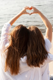 Two female friends making the love sign by the lake