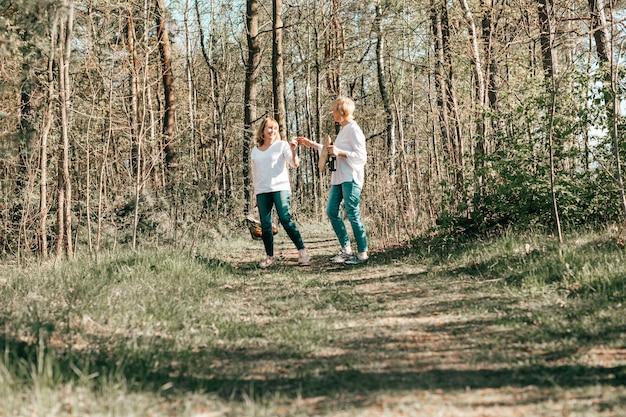 성숙한 두 여자 친구가 숲을 걷고 있습니다. 활동적인 라이프 스타일, 취미