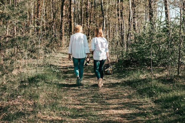 성숙한 두 여자 친구가 숲, 후면보기를 걷고 있습니다. 활동적인 라이프 스타일, 취미